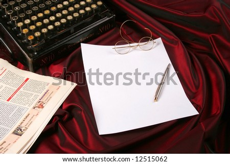 Blank sheet of paper with pen, glasses, newspaper and an old typewriter - stock photo