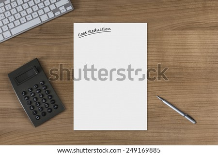 Blank sheet with the headline Cost Reduction on a wooden table with modern keyboard calculator and silver pen - stock photo