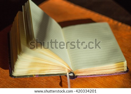 Blank sheets of opened notebook in sunlight