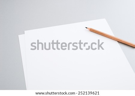 Blank sheets of paper with pencil (shallow depth of field) - stock photo