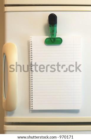 Blank shopping list on fridge - stock photo