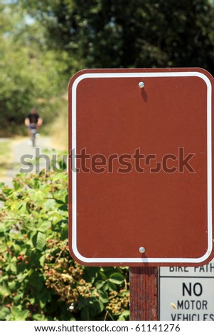 Blank sign in a public park with unidentifiable rider on bike in distant background - stock photo