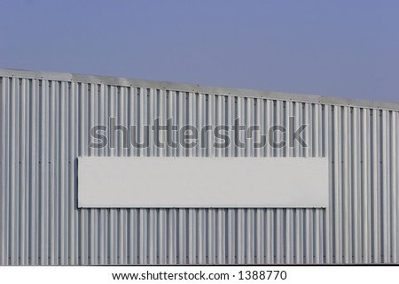 Blank sign on a factory wall.