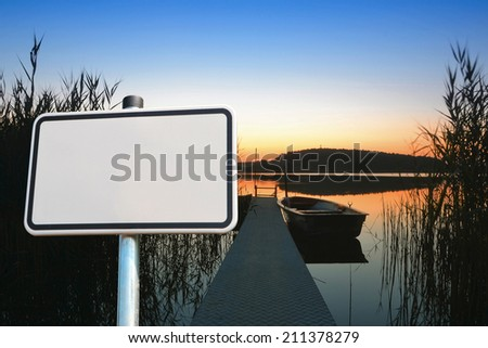 blank sign on a lake in Brandenburg in the evening after sunset - stock photo