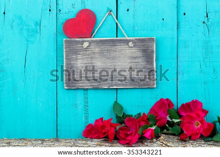 Blank sign with red heart by red roses on log border hanging on antique teal blue rustic wooden background - stock photo
