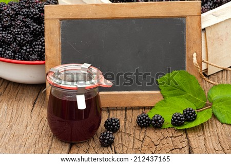 Blank slate blackboard in front of ripe blackberries and a jar blackberry jelly on a rustic wooden table - stock photo