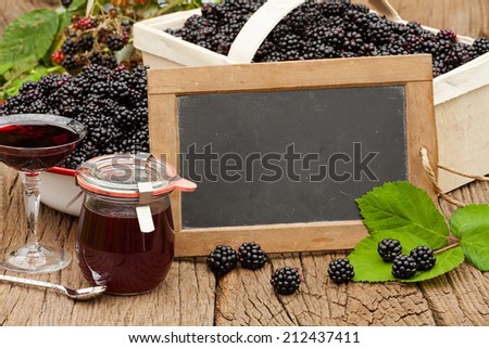 Blank slate blackboard in front of ripe blackberries, blackberry liqueur and a jar blackberry jelly on a rustic wooden table - stock photo