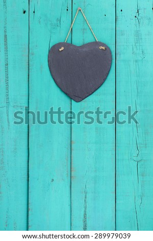 Blank slate heart hanging from rope on rustic antique teal blue wood background - stock photo