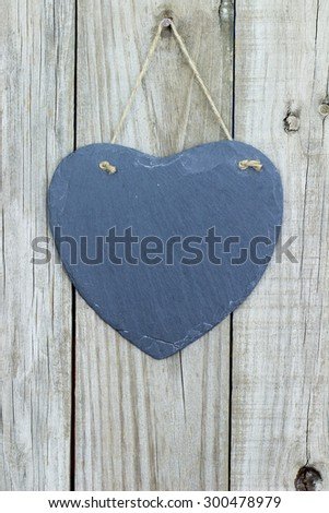 Blank slate heart hanging on rustic antique wooden background - stock photo