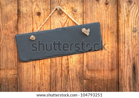 Blank slate sign hanging on a rustic wooden background - stock photo