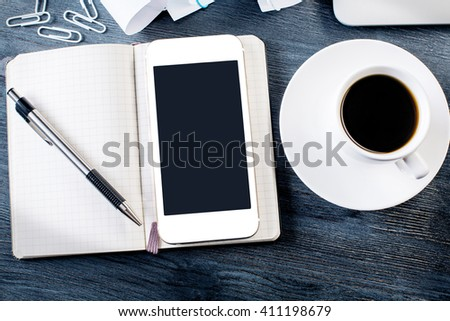 Blank smartphone on top of notepad placed on dark wooden table with ceramic coffee cup and other items. Mock up