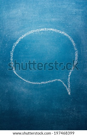 Blank speech bubble on blue chalkboard - stock photo