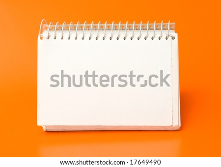 blank spiral calendar over an orange background - stock photo