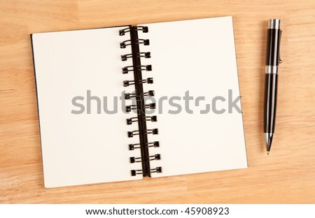 Blank Spiral Note Pad and Pen on Wood Background. - stock photo