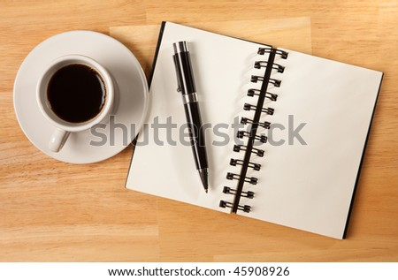 Blank Spiral Note Pad, Cup of Coffee and Pen on Wood Background. - stock photo