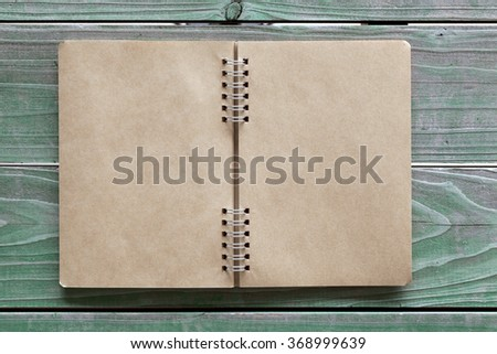 blank spiral notebook on grunge wood background  - stock photo