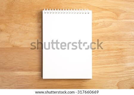 Blank spiral notebook on wood background - stock photo