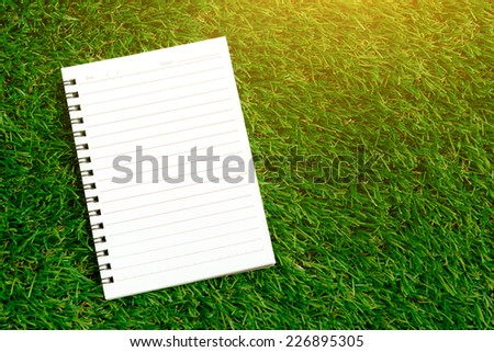 Blank spiral notebook with line paper on green grass - stock photo