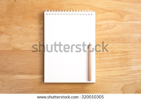 Blank spiral notebook with pencil on wood background - stock photo