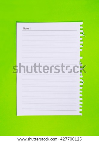 Blank stack white note paper on green background.