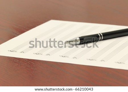 Blank staff paper and mechanical pencil on a wooden desk. - stock photo