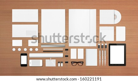 Blank Stationery Corporate ID set on wooden background with soft shadows. Consist of Business cards, A4 letterheads, Folder, Tablet PC, envelopes, tube, phones, disk and notebook. - stock photo