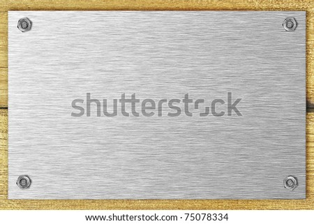 Blank steel plate bolted to a wooden surface - stock photo