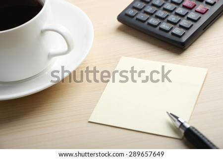 Blank sticky note is on the table with calculator and coffee aside.