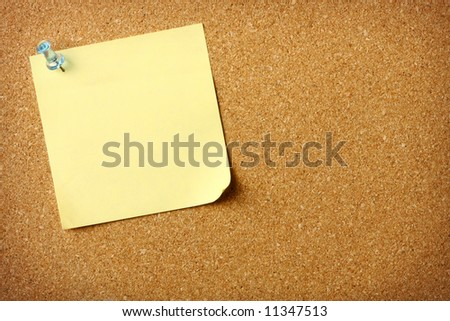 Blank sticky note pinned to corkboard background - stock photo