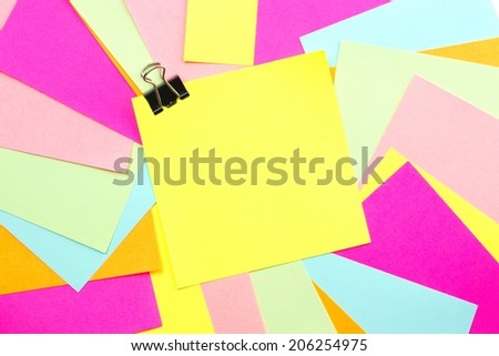 Blank sticky note with paper clip and colorful background  - stock photo