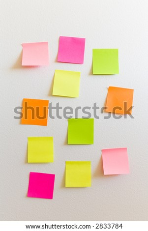 Blank sticky notes attached to a white wall - stock photo