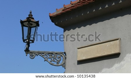 Blank stone tablet and old lamp on the wall - stock photo