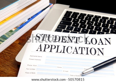 blank student loan application on desktop with books and laptop - stock photo
