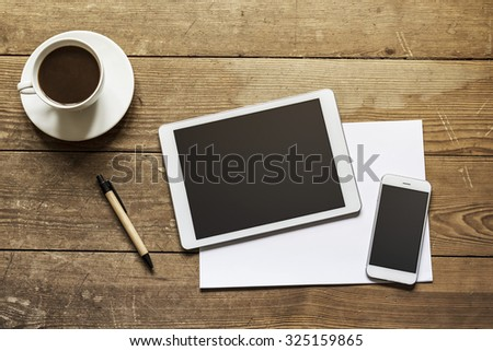 blank tablet and phone over empty white paper on a wooden workspace - stock photo