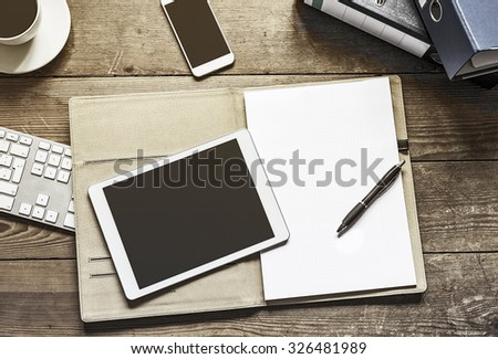 blank tablet and phone with an empty folder on a wooden workspace - stock photo