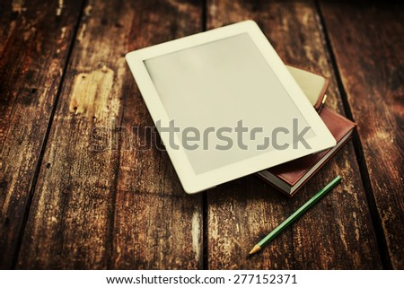blank tablet device over a wooden workspace table/ selective focus - stock photo