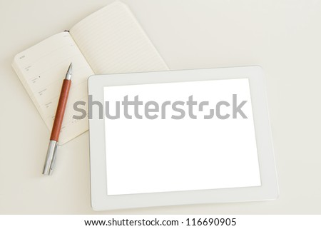 blank tablet pc with open notebook and pen - stock photo