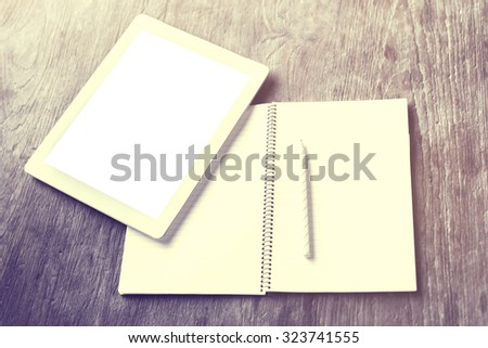 Blank tablet with blank diary and pen on a wooden table