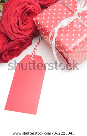Blank tag, gift box and red roses isolated on white background. Top view - stock photo