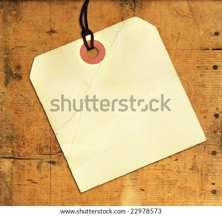 Blank tag on weathered wood with rusty nails and cracks for background texture.