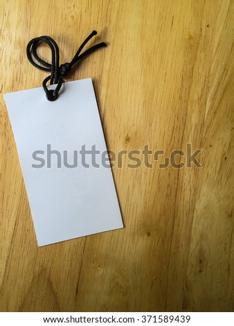 Blank tag tied on wooden background for text.Price tag,gift tag,sale tag,address label? - stock photo