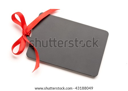 Blank tag tied with red ribbon bow on white background. Price tag,place card,gift tag,address label,etc. - stock photo