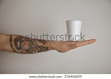 Blank take away paper glass on tattooed brutal man hand, side view presentation isolated on white background - stock photo