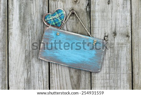 Blank teal blue antique wood sign with country fabric heart hanging on rustic wooden background - stock photo