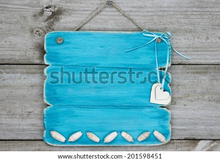 Blank teal blue sign with seashells and hearts hanging on rustic wooden background - stock photo