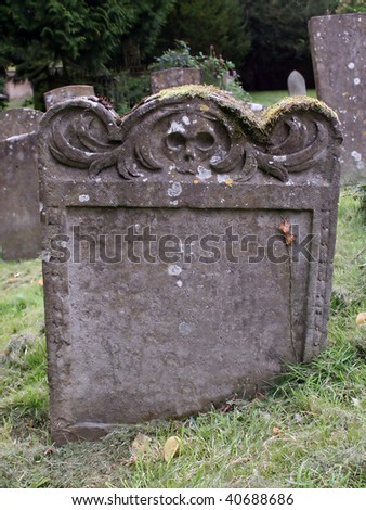 Blank Tombstone Engraved with Skulls - stock photo