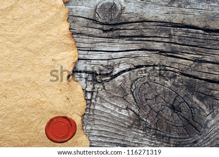 Blank torn paper with wax seal on old wooden background - stock photo