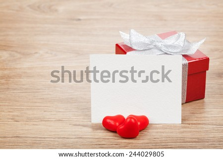 Blank valentines greeting card, gift box and red candy hearts on wooden background - stock photo