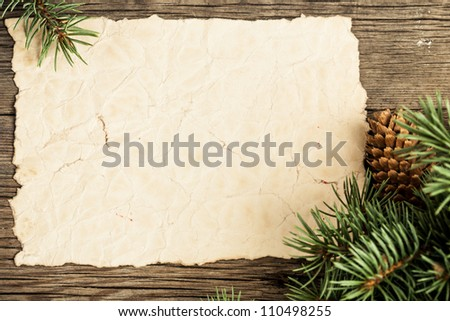 Blank vintage paper framed branch of Christmas tree on wood - stock photo