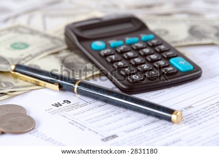 Blank W-9 income tax form with pen, calculator and american dollars - stock photo